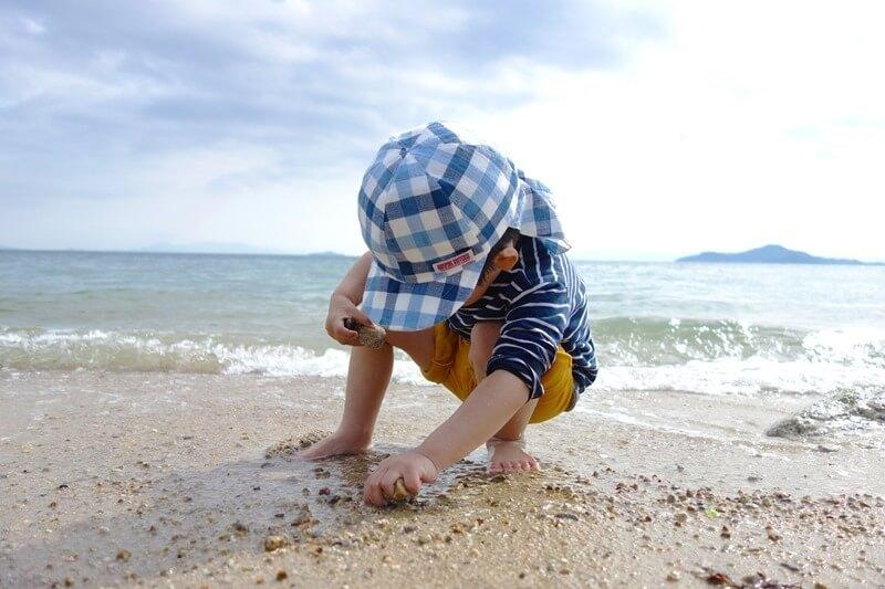 サンビーチおきみ前のビーチで電車ごっこをする息子