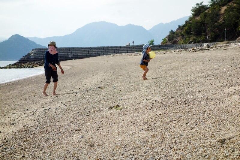 サンビーチおきみ前のビーチを走り回る息子と母