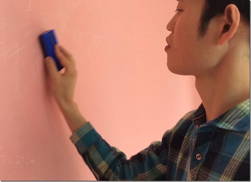 黒板消しを使って落書きを消す様子。