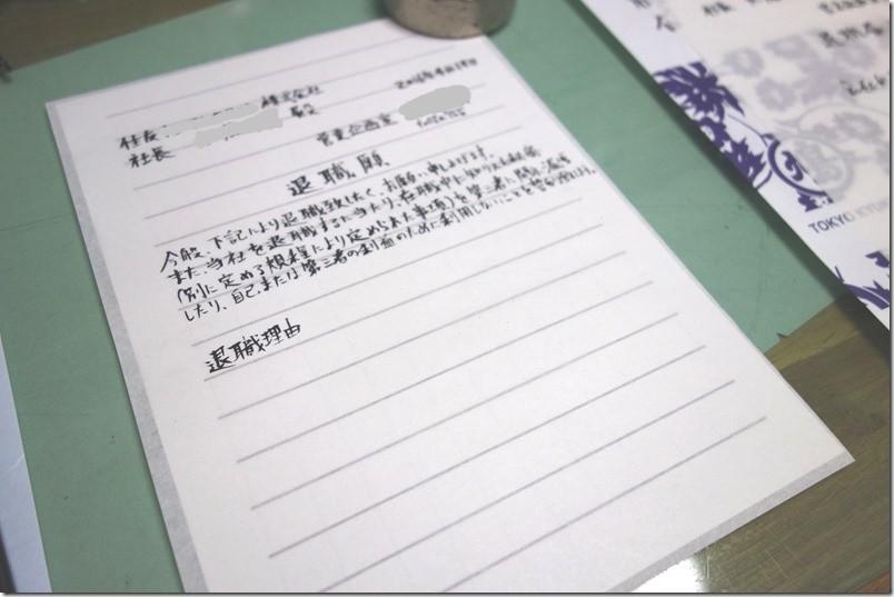 手書きの退職願 / 退職届を筆ペンで書き進める。